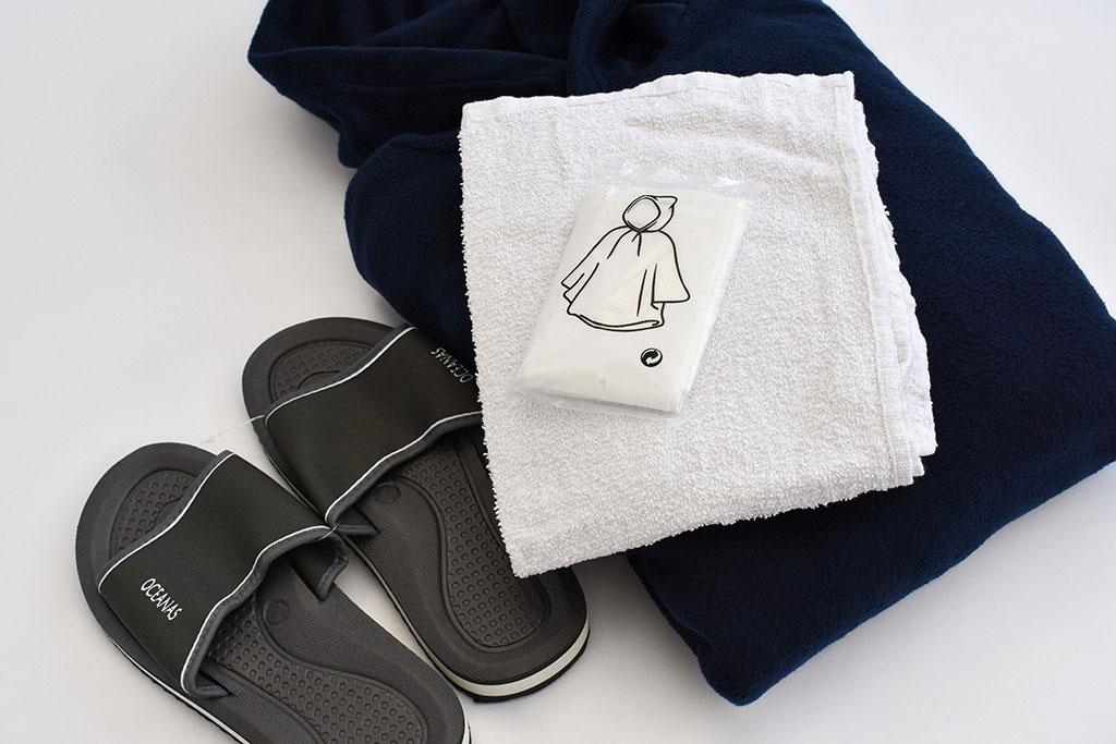 CBRN beschermingsmiddelen van IMG Europe, zoals een noodkledingset met fleecebroek, fleeceshirt, slippers, regenponcho en voorgewassen handdoek